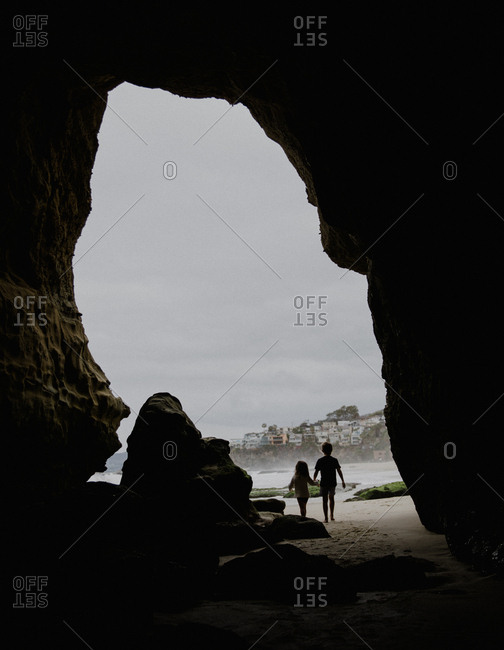 Siblings holding hands in a cave in Laguna beach
