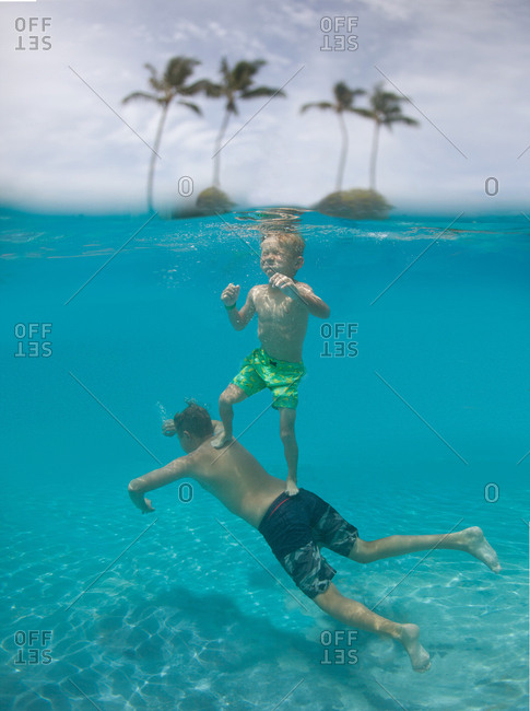Underwater view of boy riding on brother's back in Hawaii