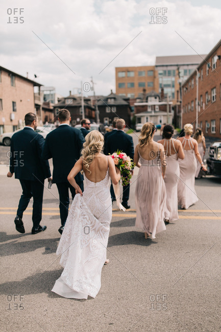 Wedding party walking through parking lot for photo session