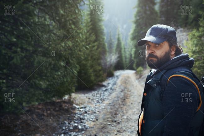 Globetrotting man exploring mountain forest