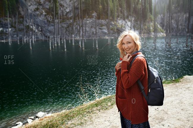 Blond woman exploring Kaindy Lake, Kazakhstan