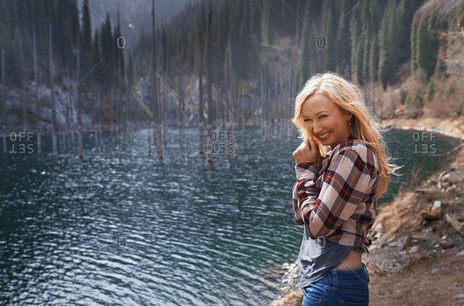 Happy woman at the mountain lake with submerged trees