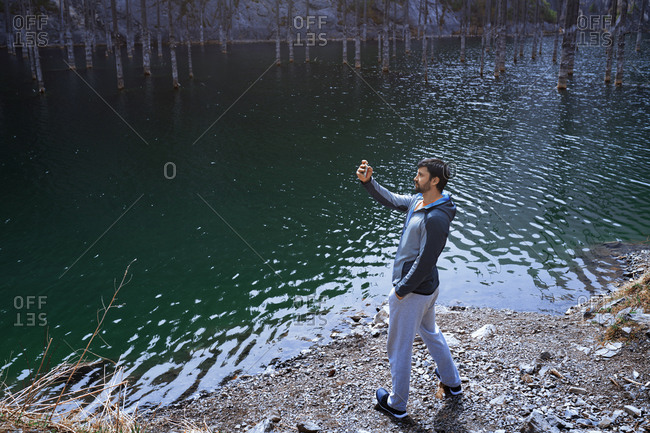 Man taking picture with smartphone at the Mountain lake