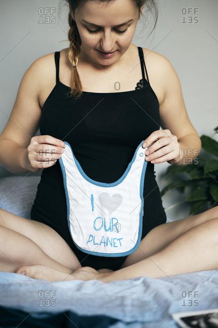 Pregnant woman preparing baby clothes.