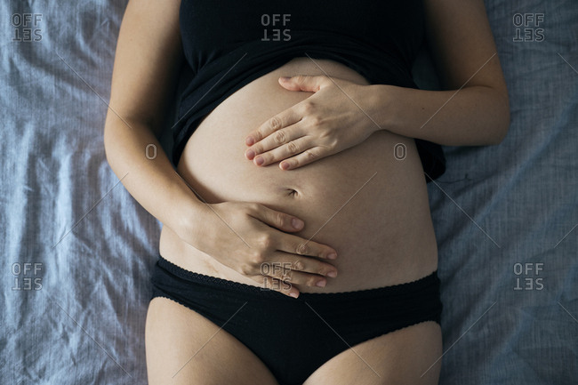 Pregnant woman making heart-shaped gesture on her belly.