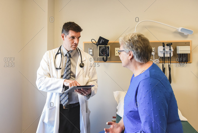 Doctor holding tablet speaking to older patient in a clinical setting.