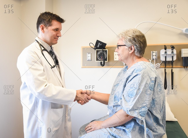 Doctor shaking hands with older patient wearing gown in clinic.