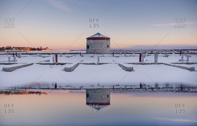 Tower and docks at sunset on waterfront of Kingston in winter.