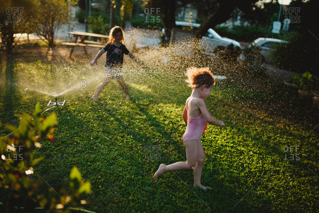 Two girls wearing bathing suit playing on the grass with sprinkler