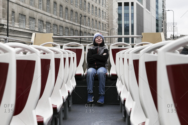 Happy Tween Boy Sits Alone in Back Row on Top of Double Decker Bus