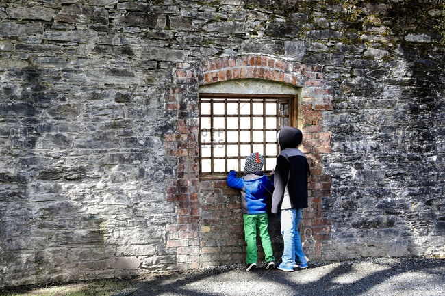 Tween Boy and Younger Brother Look Through Iron Window in Stone Wall