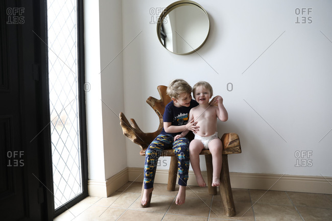 Happy Brothers Hug While Sitting on Indoors Organic Wooden Bench