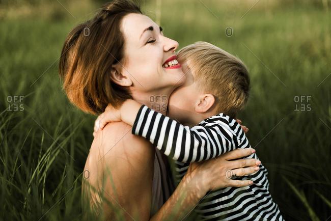 Mother hugs her little son outdoor