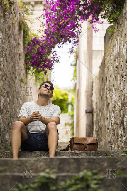 A man in sunglasses sits on stone steps in an alleyway in Dubrovnik.