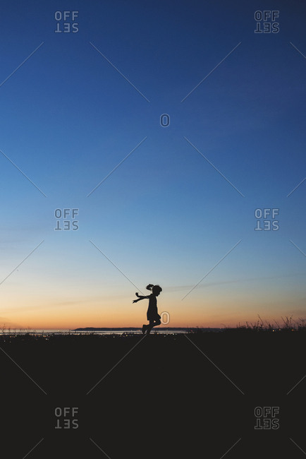 Silhouette of a young girl skipping at sunset near San Diego, CA