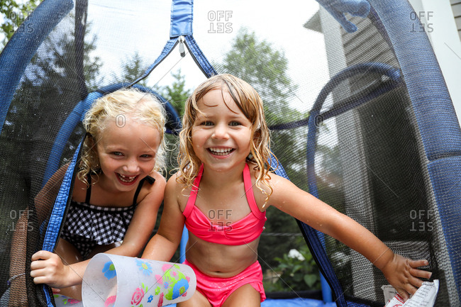 sisters laughing having water fight on trampoline in summer
