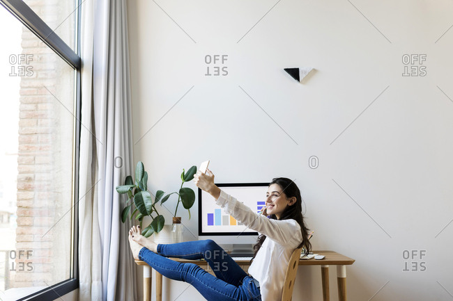 Female Model taking a selfie At Home Office