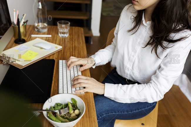 young Woman typing and having lunch at her home office
