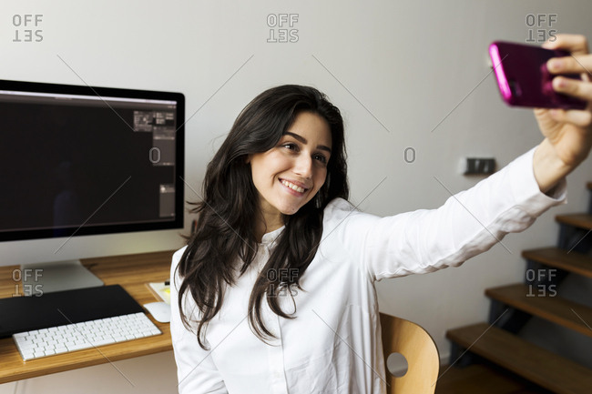 young women taking a selfie while sitting in her home office