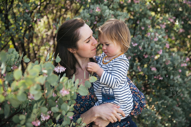 A young mother holds her toddler daughter among manzanita blossoms
