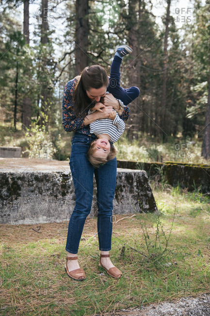 A young mother holds her toddler daughter upside down on a concrete bunker with trees in the distance