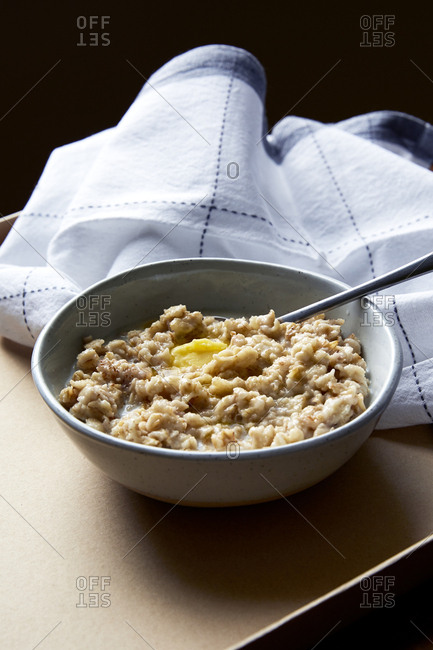Bowl of cooked oatmeal porridge with milk and butter,