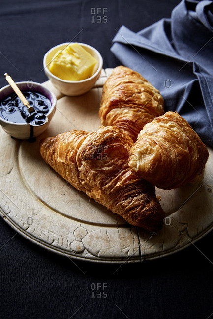 Freshly baked croissants with berry jam and butter,