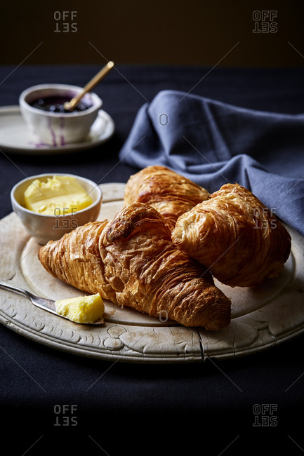 Fresh Croissants on round wooden board with butter and jam,