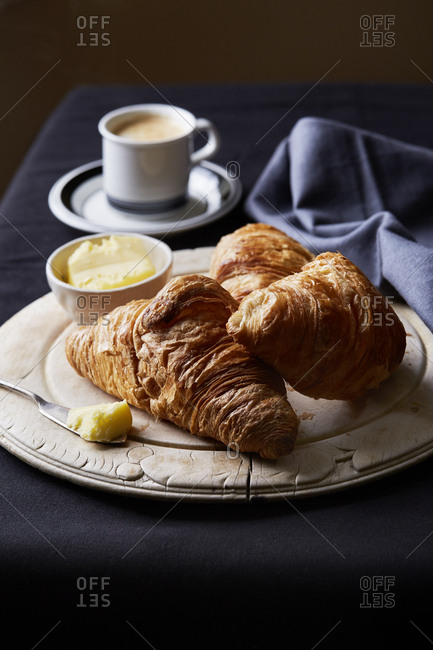Croissants with butter on a round wooden board with hot coffee,