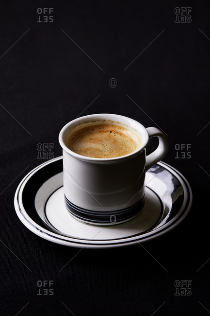 One espresso on a black table cloth