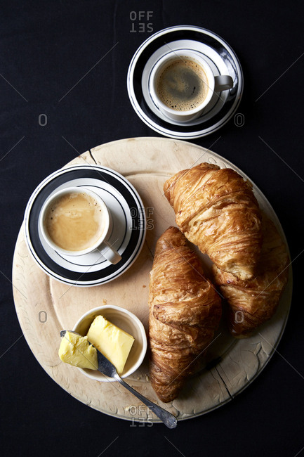 Croissants on wooden board with butter and two espresso?s,