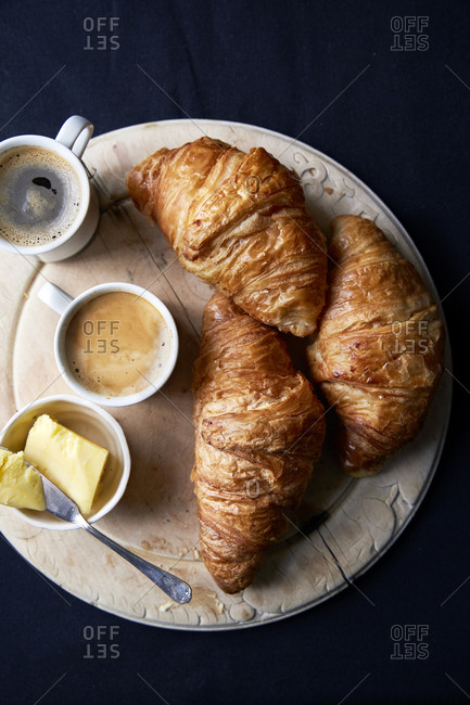 Croissants on a round wooden board with butter and two espresso?s,