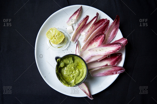 Radicchio leaves with a green herb dip and a squeezed lemon,