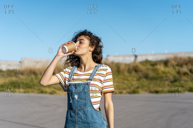 Young woman drinking coffee from a disposable cup