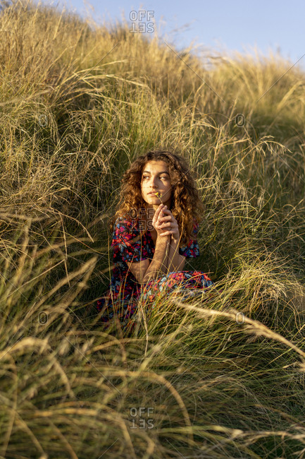 Pensive young woman crouching in meadow