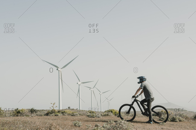 Spain- Lanzarote- mountain biker on a trip in deserted landscape with wind turbines in background