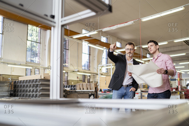 Two men discussing plan in a factory