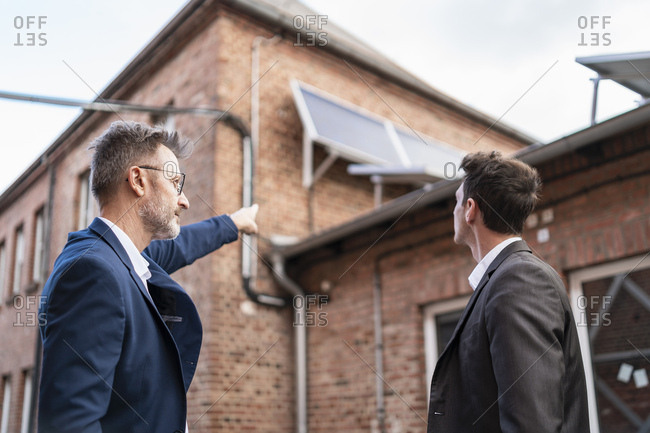 Businessman pointing at solar panels on brick building