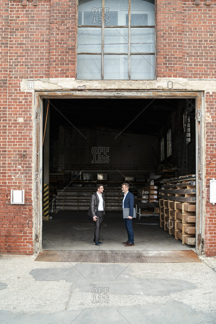 Two businessmen talking at an old storehouse