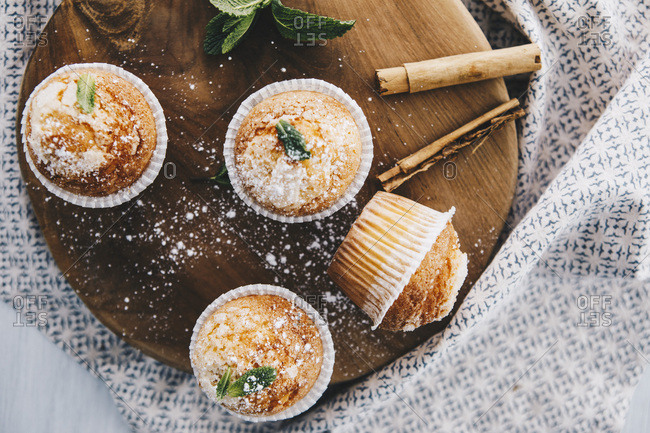 Home-baked muffins with cinnamon and mint on wooden board