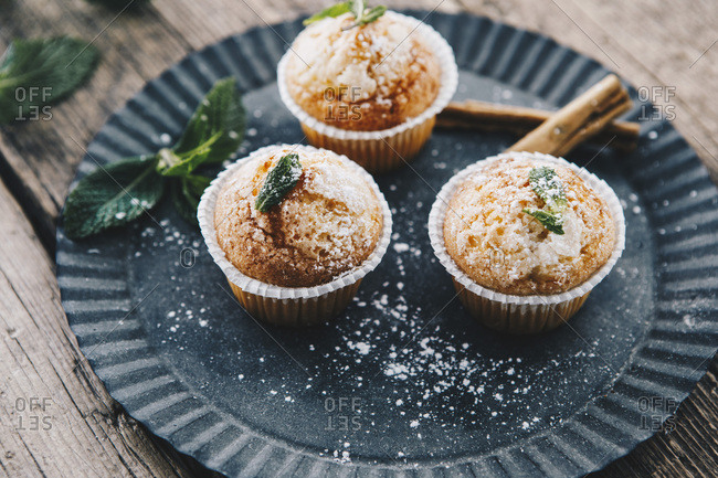 Home-baked muffins with cinnamon and mint on plate