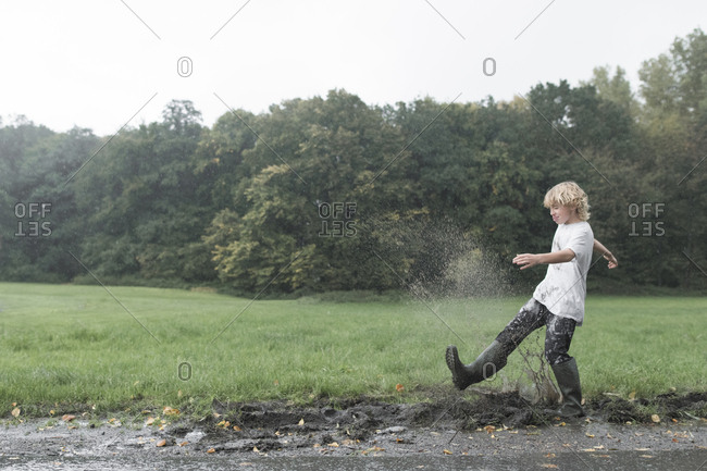 Boy splashing with dirty water of puddle