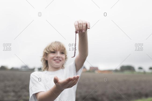 Boy's hand holding earthworm