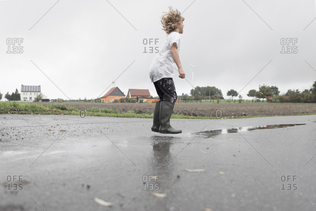 Boy jumping into a puddle