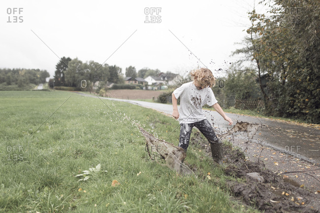 Boy jumping into a muddy puddle