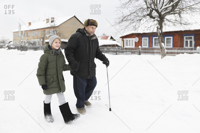 Grandfather and grandson walking together in snow