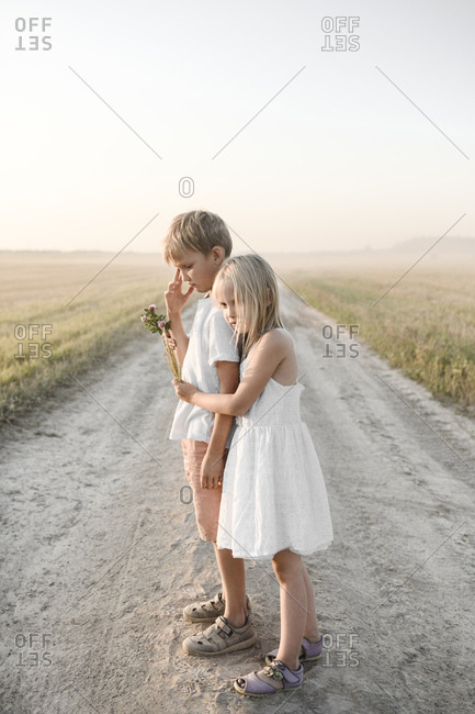 Girl hugging boy on a rural dirt track
