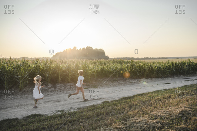 Girl and boy running on a rural dirt track along cornfield
