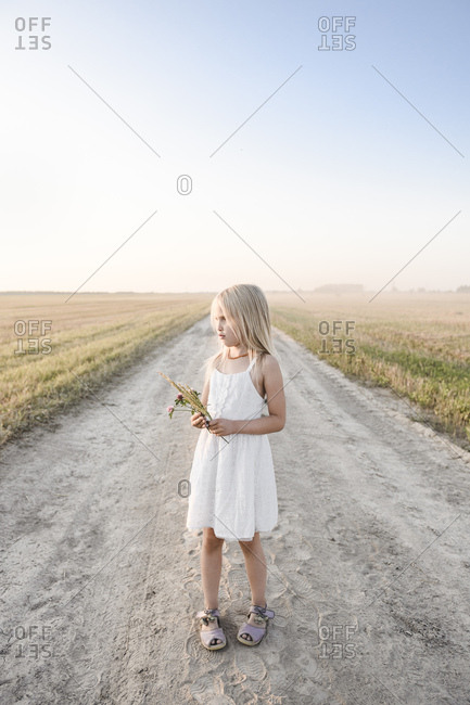 Girl standing on a rural dirt track