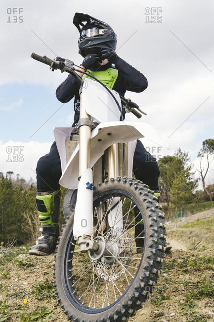 Motocross driver putting on helmet